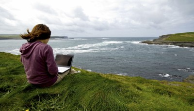 Girl with computer next to ocean