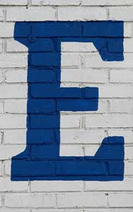 blue letter E painted on white brick wall