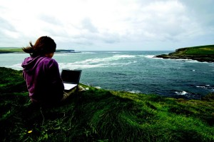 Woman by sea with computer
