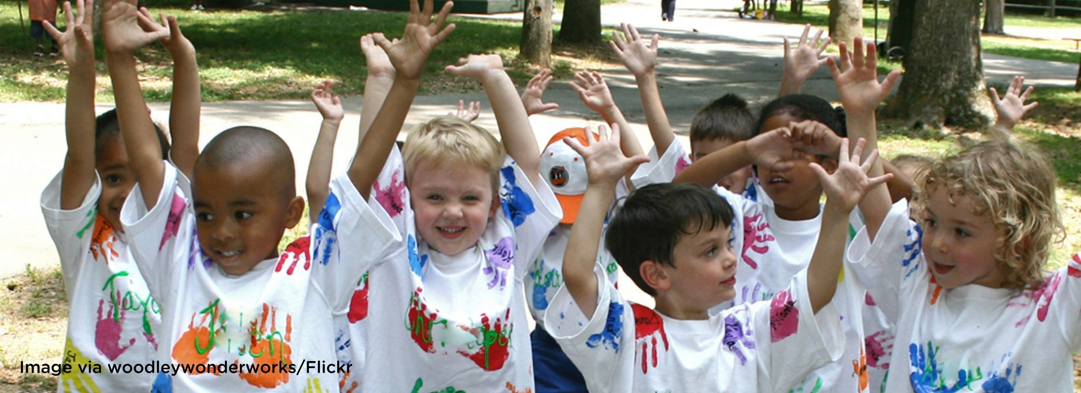 Children wearing handprint t-shirts and raising their arms high