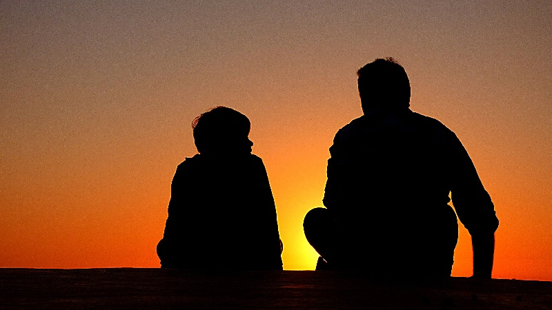 father and son talking in front of sunset