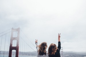 two girls holding up peace signs toward a bridge