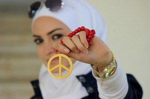 woman in hijab with sunglasses holding out peace sign jewelry