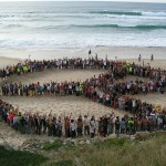people forming a peace sign on the beach