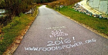 Asphalt pathway with vegan message chalked on it