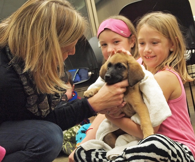 Karen Patterson and two girls holding a puppy
