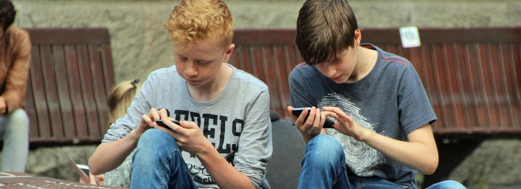 teens sitting on a curb using mobile devices