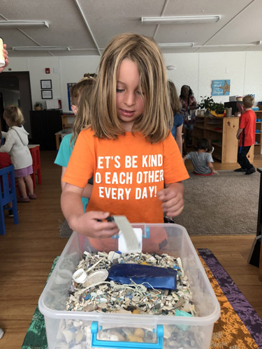 Kindergarten student Joshua looks through a box of plastic waste collected from the ocean.